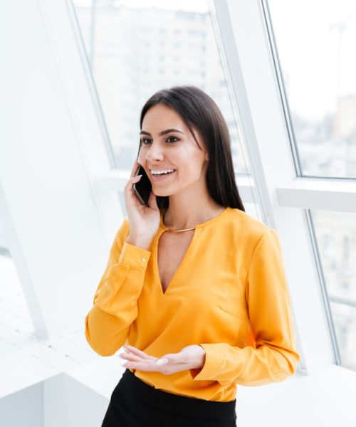 Business woman in orange shirt standing near the window and talking at phone in office